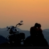This couple enjoys a romantic moment alongside their motorcycle as they watch the sun set behind the peaks of the Wichita Mountains from atop Mount Scott in Lawton.