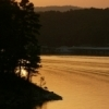 The setting sun bathes scenic Broken Bow Lake in a golden glow at Beavers Bend State Park.