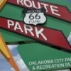 A retro-styled sign points the way to the Route 66 Park in Oklahoma City.  The park is situated along the Mother Road and features a playground, interpretive plaza, a watchtower looking over Lake Overholser, wetlands with boardwalks and more.