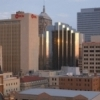 A gleaming building in the Oklahoma City downtown area reflects the setting sun.
