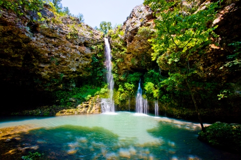 The cascade at Natural Falls State Park in northeast Oklahoma plummets 77 feet into an oasis of lush ferns and trees. A hiking trail leads down to the grotto area where deck seating is available so visitors can sit and enjoy the view.