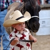 A future rodeo star leads his trusty horse into the arena at Rodeo Miami.