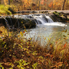 Waterfalls flow amidst colorful fall foliage at the Chickasaw National Recreational Area in Sulphur.