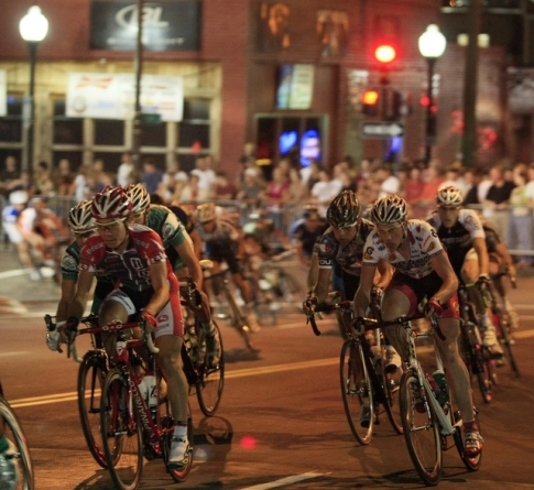 Bicyclists race toward the finish line under the glow of nighttime Tulsa during the annual Tulsa Tough Ride & Race.