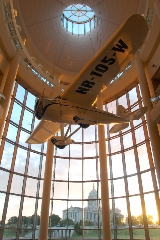 A replica of the Winnie Mae airplane piloted by Wiley Post is suspended in the rotunda of the Oklahoma History Center above a view of the state capitol building.