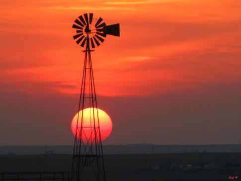 A cloudy sunset in the Oklahoma panhandle provided an awesome display of the sun as it was setting next to a windmill in Texas County near Guymon.