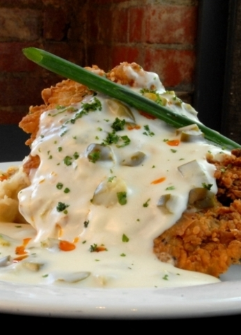 The traditional chicken-fried steak takes on a contemporary edge at Cheever's Cafe in Oklahoma City where it is served over red-skinned garlic mashed potatoes with jalapeno gravy.