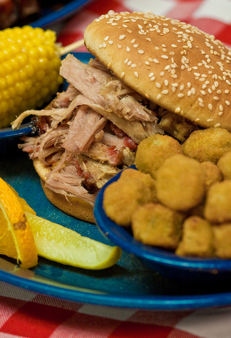 A pulled pork sandwich with fresh corn and fried okra at Dink's Pit Bar-B-Que in Bartlesville.
