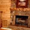Rustic paneling and a stone fireplace adorn the cozy living area inside Timber Rock Lodge at Broken Bow Lake Cabin Rentals in Broken Bow.