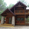The charming exterior of the Honey Bear Cabin at Beavers Bend Adventures in Broken Bow.