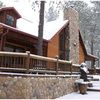 A dusting of winter snow coats the charming Running Bear Lodge located at Beavers Bend Adventures in Broken Bow.