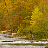 A fly fisherman casts his line at Lost Creek in Beavers Bend State Park amidst gorgeous fall foliage.