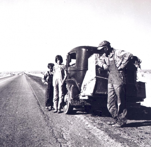 A family lingers on the side of the highway near their car and meager belongings on the great trip west during the 1930s Dust Bowl.