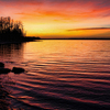 The glowing colors of a fiery sunset fill the skies and reflect on the waters of Lake Eufaula.