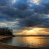 Golden rays and clouds create a tranquil and picturesque sunset over a cove of Lake Eufaula.