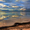 A cloudy sky reflects on the still surface of Lake Eufaula creating a stunning scene with wrap-around shades of blue.