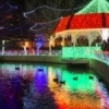 Lights strung around the gazebo at Rhema Christmas Lights in Broken Arrow reflect on the pond's surface on a cold winter day.