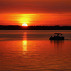 Boaters enjoy a peaceful evening on Lake Eufaula as the sunset bathes the scene in glowing hues.