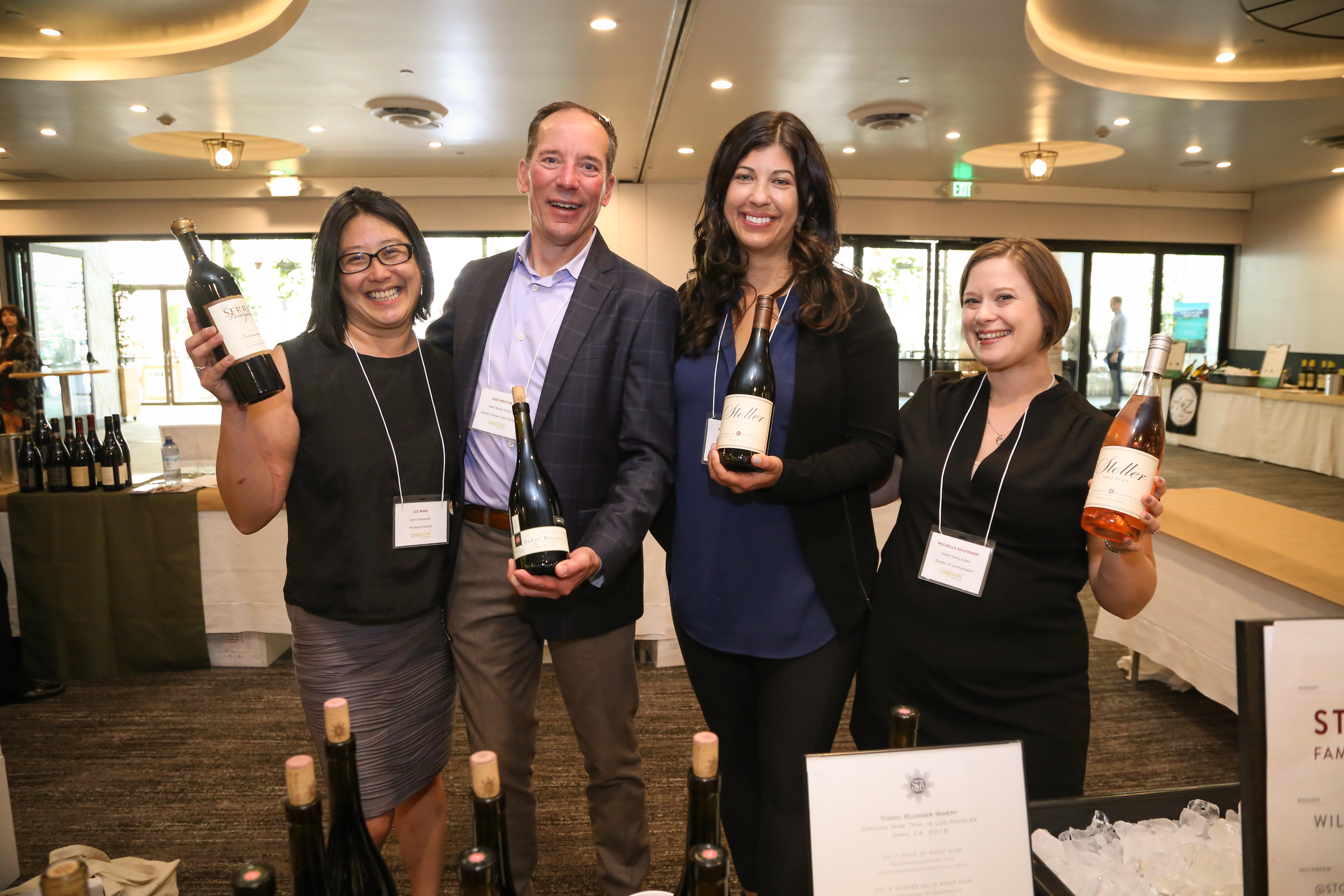 Group of 4 Oregon wine producers holding bottles at event