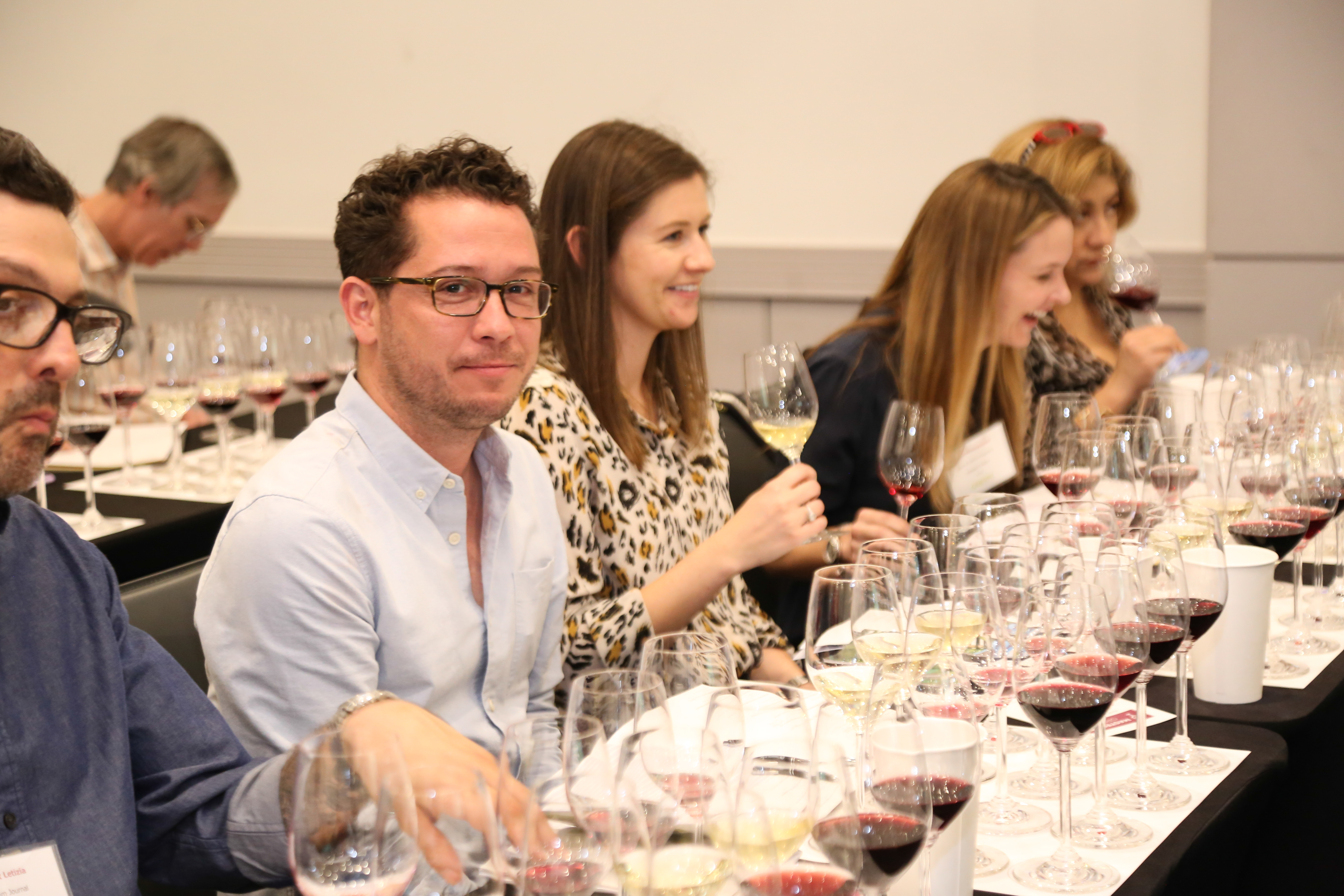Man at a wine master class with many glass of wine in front of him