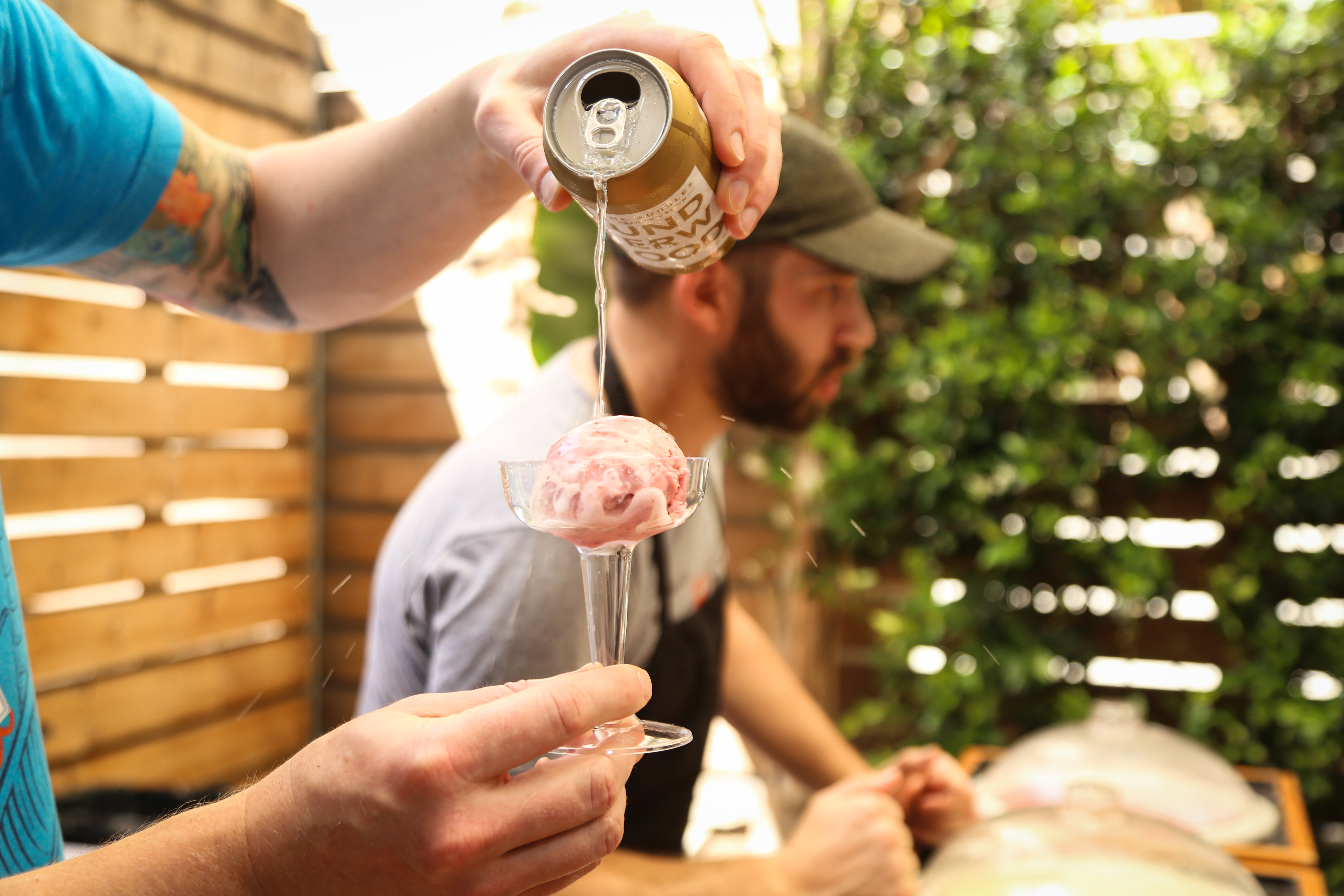 Man pouring a can of sparkling wine over ice cream