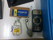 Figure 2: From left to right the equipment is, a bottle of Robert's Mineral Oil, The Oil applicator and a multimeter, above is the micrometer and it's container.