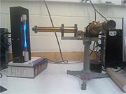 Figure 1: The overall setup. The spectrum tube power supply and mercury tube are to the left, with the constant-deviation spectrometer's slit aimed at the mercury tube and the viewing scope positioned for the experimentalist.