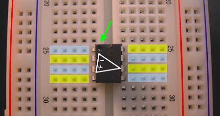 An integrated circuit chip plugged into a breadboard.