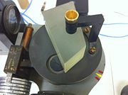 Figure 2 - Calibration Crystal/Prism: This is the prism located at the center of the spectrometer. Because the ocular portion and the slit portion of the spectrometer are fixed, the prism is what is adjusted in order to calibrate, and then rotated with the wavelength dial, which can be seen at the lower left hand corner. We loosened the screw on top of the prism and then rotated it by hand in order to calibrate the spectrometer to the Mercury spectral lines. We were also careful not to change the position of the prism.