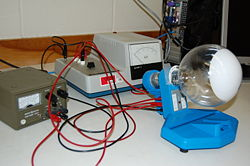 Figure 1: Apparatus for electron diffraction experiment showing the two used power supplies and connections to the diffraction apparatus.  The multimeter was wired between the positive high high voltage port (on the left side of the Teltron power supply) and the G7 port on the diffraction apparatus.Image Courtesy Physics307L[7]
