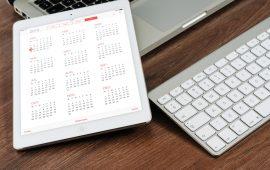iPad with calendar app open on a desk near a laptop computer