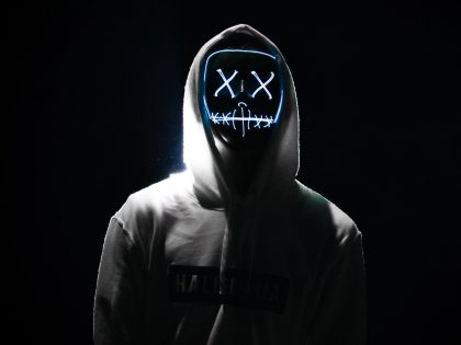 Hacker wearing a gray hoodie and mask