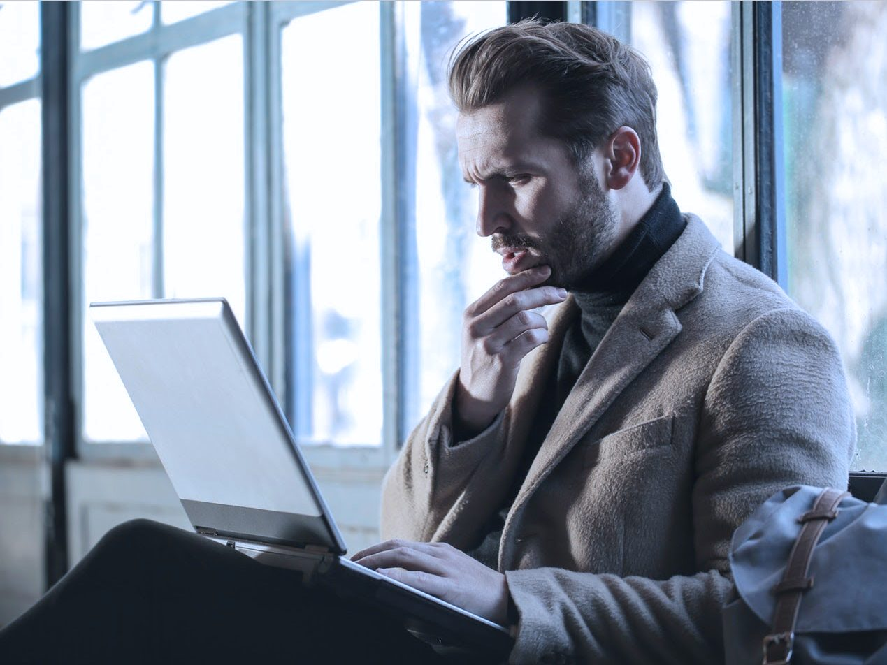 Businessman with laptop staring in disbelief at email bomb