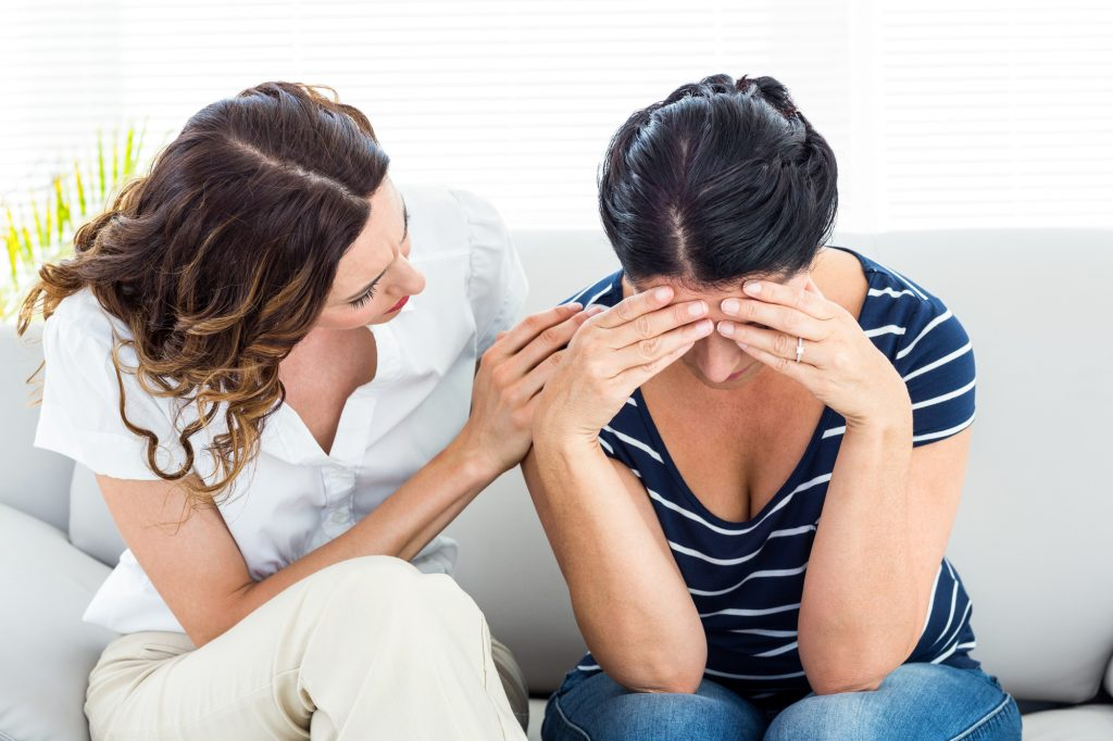 Therapist comforting her patient on white background