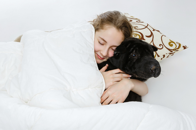 Teen girl sleeping with dog