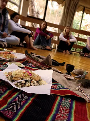 traditional andean despacho ceremony held by paco juan gabriel with coca leaves during women's ayahuasca retreat in the sacred valley cusco peru.