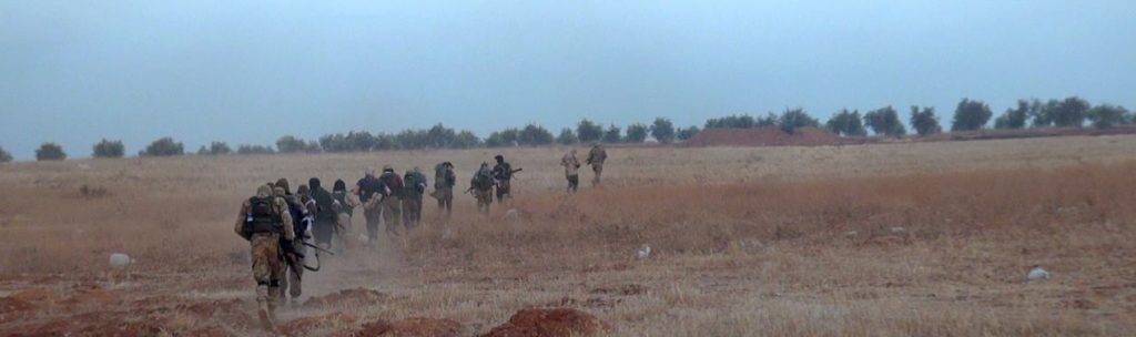 "Jabhat al-Nusrah ""inghimasiyeen"" (shock troops) sprint at the enemy in south Aleppo. Source: Screenshot taken by author."