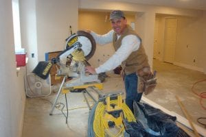 14202374-contractor-installing-new-baseboard-with-bull-nose-corners-and-new-laminate-flooring-renovation-abst