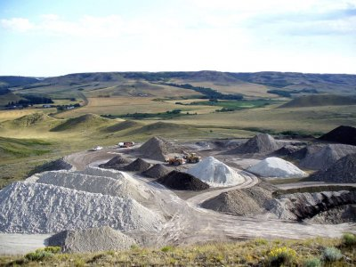 Stockpiles of clay and wheel loaders on the flattened hill