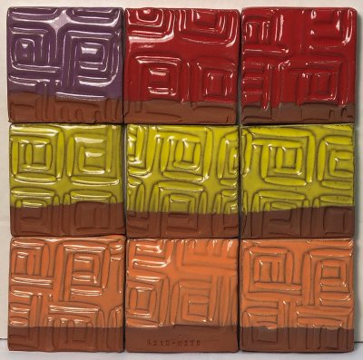 Four tiles of a red-burning clay covered with purple, yellow, orange, black glazes