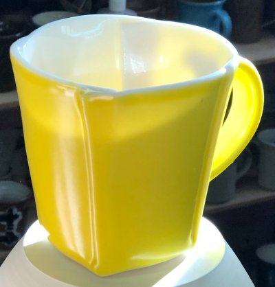 A slab-built porcelain mug with yellow glaze showing off its translucency in sunlight