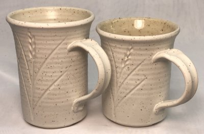 Two matte glazed mugs on a speckled body