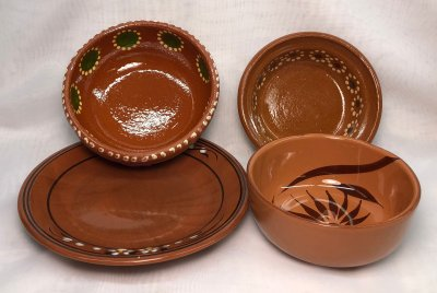 Terra cotta bowls behind stoneware ones emulating their appearance