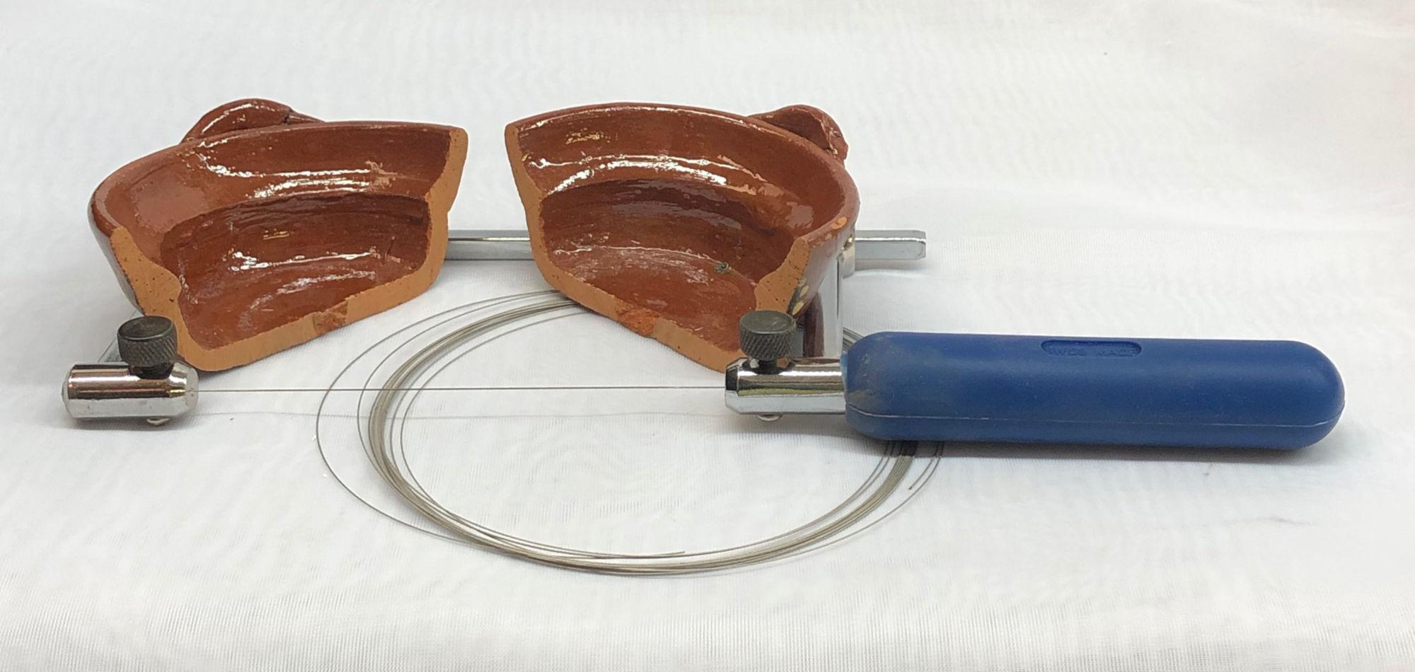 A terra cotta dish has been cut in half using a hand diamond saw