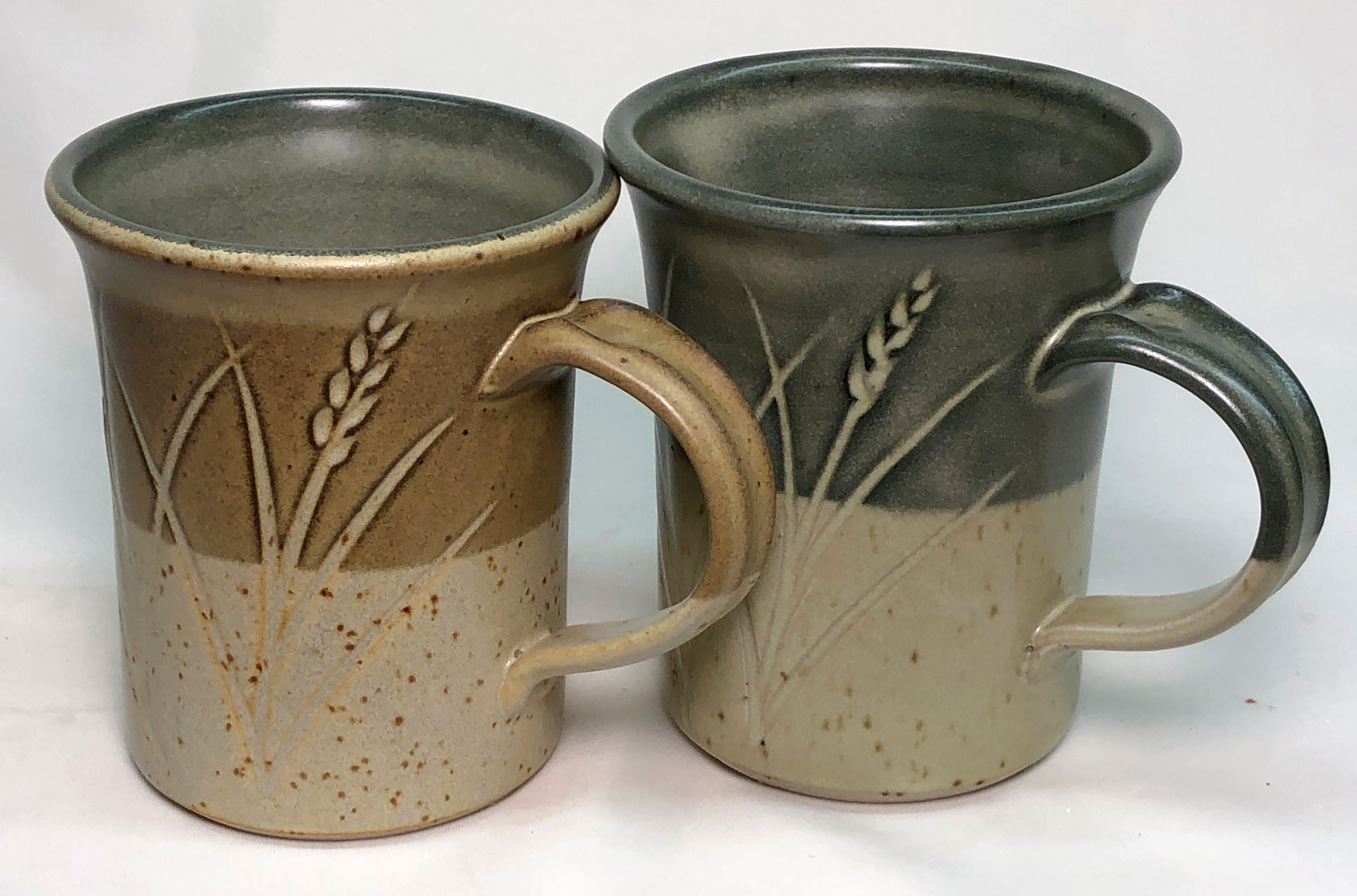 Two mugs. One  fires a rich brown over the black engobe because it has 1% iron added.