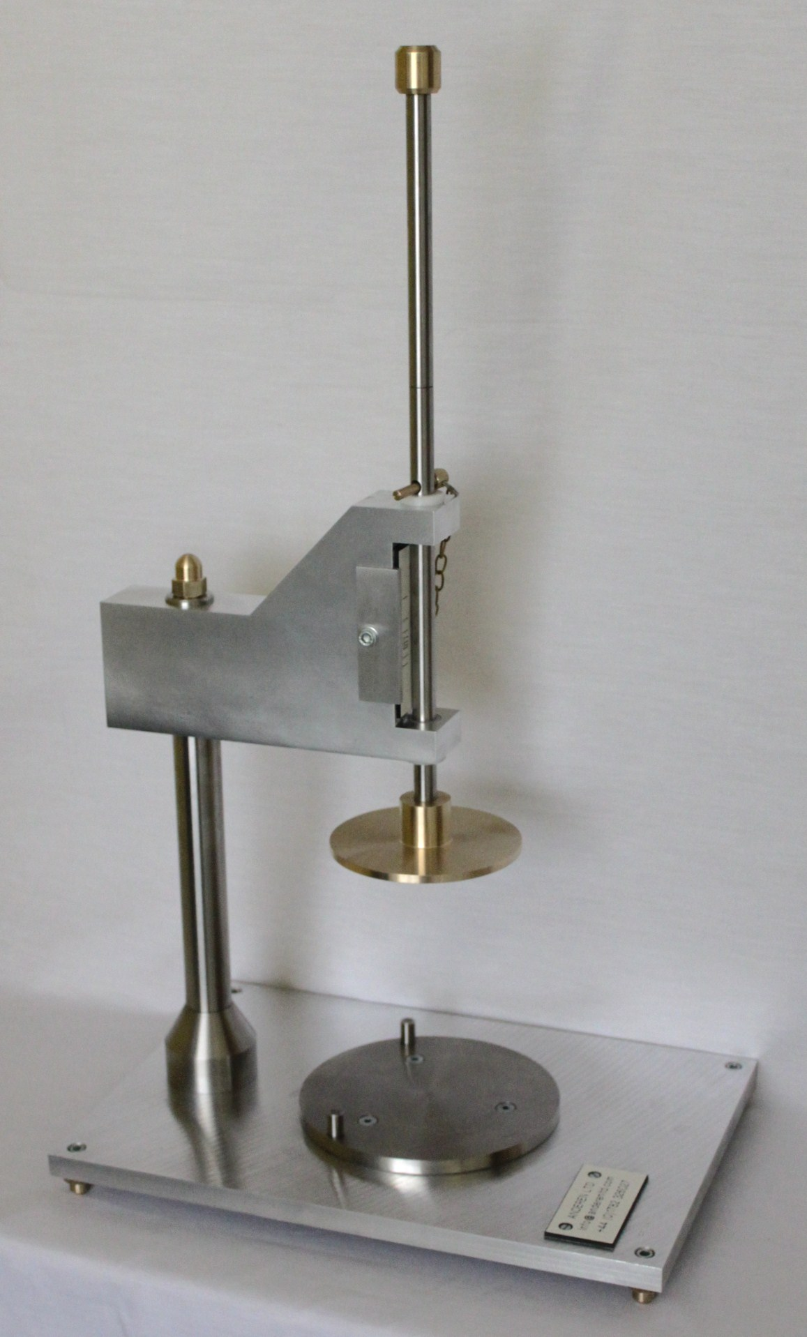 A plasticity testing device, a weighted plate falls and deforms a plastic specimen
