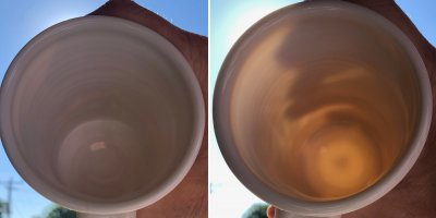 Two mugs in hand, blocking the sun, to compare their translucency