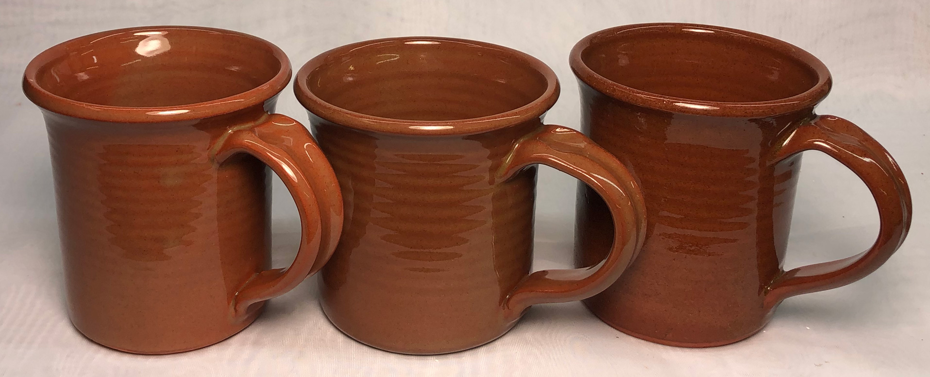 Three clear-glaze terra cotta mugs with rich red color