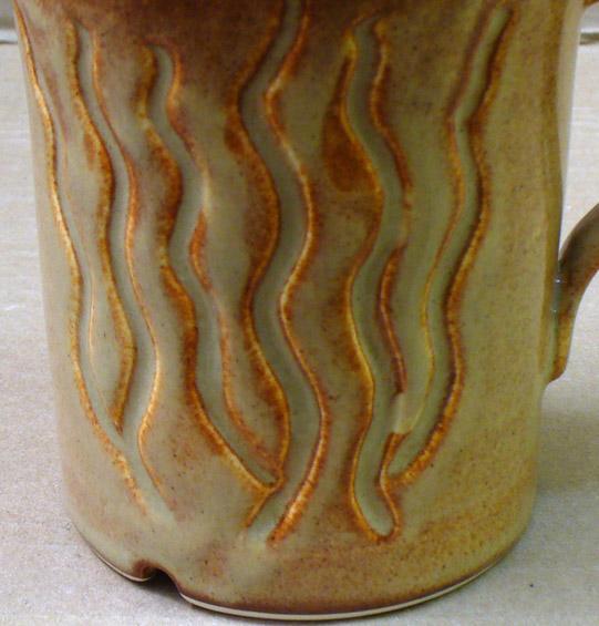 A closeup of Alberta Slip lithium brown cone 6 recipe GA6-G on a porcelain