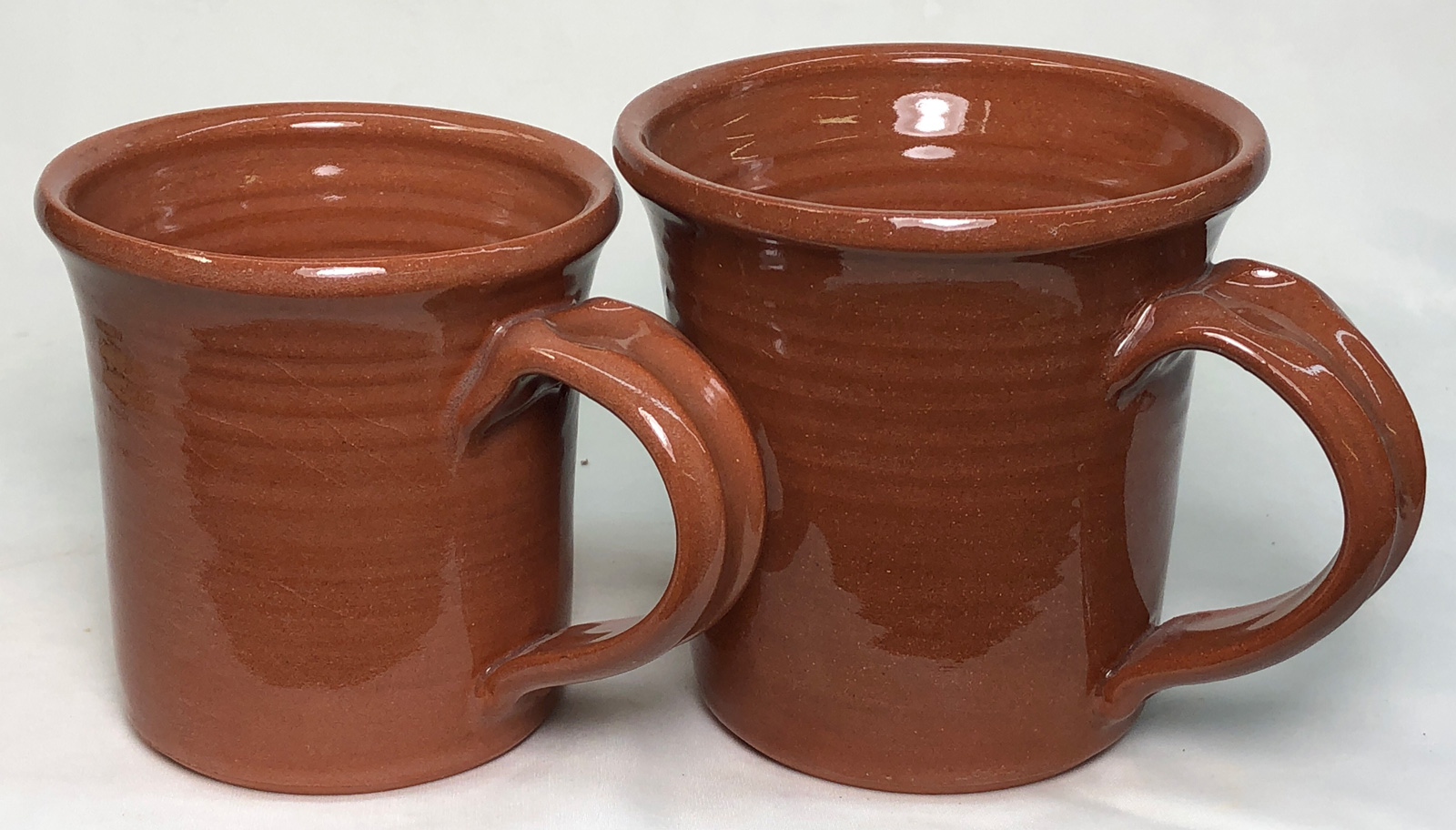 Two terra cotta mugs, the glaze on one is more glossy and the body color is richer